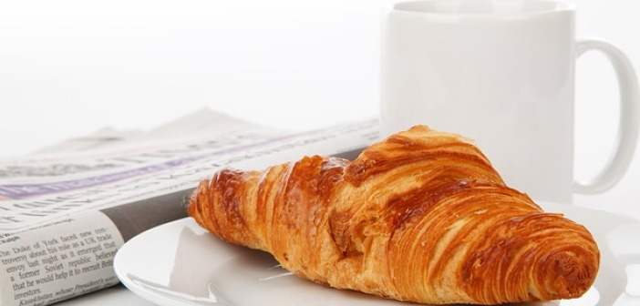 Image of Croissant coffee mug and newspaper on a desk