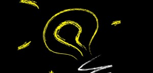 Yellow light bulb on black background