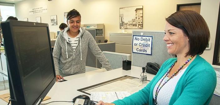 Woman bank employee helping young male