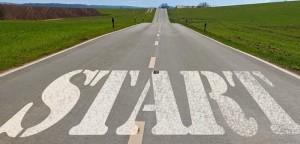 Road start sign green pastures blue sky