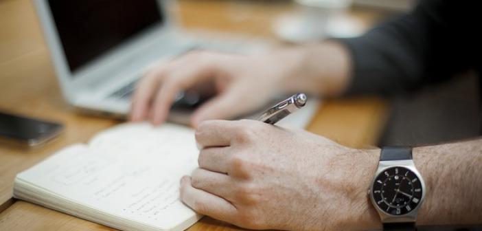 Man writing agenda laptop table