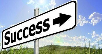 Success sign green pastures blue sky